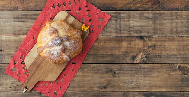 Pan de muerto on wooden background, typical mexican food. day of the dead celebration. copy space. top view.