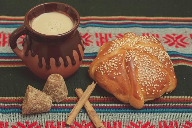Pan de muerto y taza de 초콜릿 sobre una mesa con mantel tipico mexicano