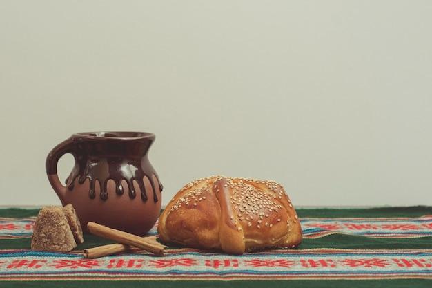 Pan de muerto y taza de 초콜릿 sobre una mesa con mantel tpico mexicano