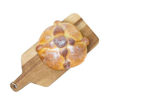 Pan de muerto on yellow background, typical mexican food. day of the dead celebration. copy space. top view.