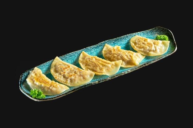 Жареная на сковороде азиатская гёза, фаршированная мясом, подается на синей тарелке японские цзяози или пельмени