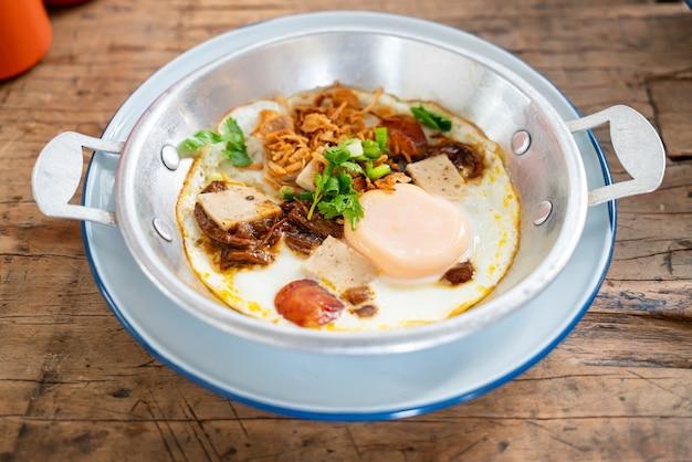 Жареное яйцо на сковороде с тайской колбасой на деревянном фоне