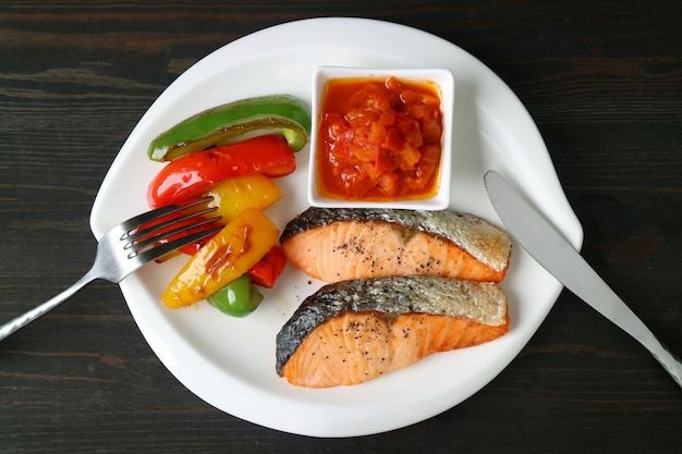 Pan fried salmon steaks with grilled colorful bell peppers and provencal sauce on white plate