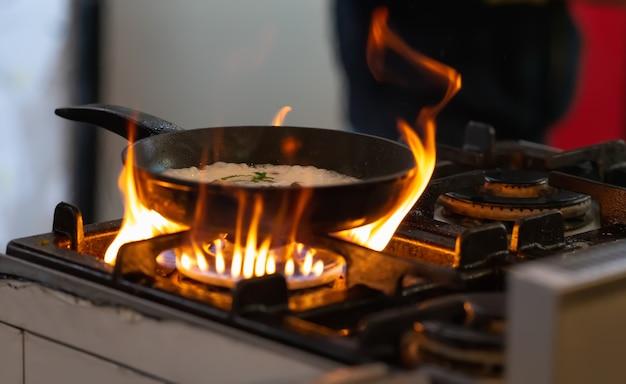 케이터링 개념의 부엌에서 뜨거운 불길 위에 가스 호브에 지글 지글 음식 팬