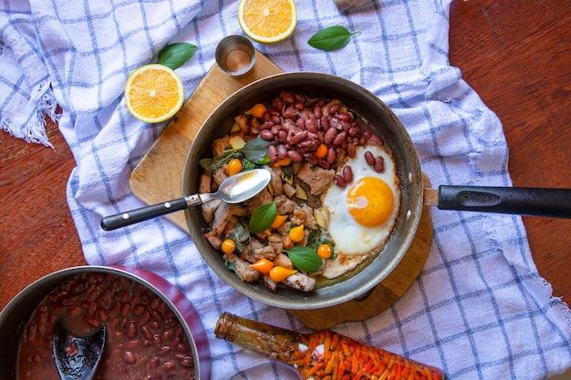 Сковорода яичница, свинина, патока, перец и базилик, фасоль с салфеткой на поверхности деревянного стола,
