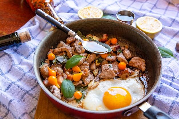 Сковорода яичницы, свинины, патоки, перца и базилика, с салфеткой на поверхности деревянного стола,
