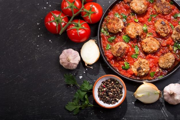 Сковорода тефтелей с томатным соусом на темном столе