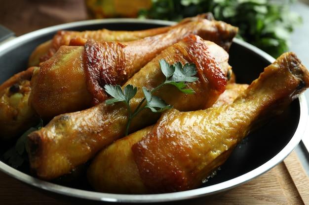 Сковорода жареных куриных голеней, крупным планом
