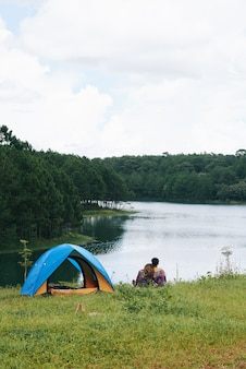 A pan shot of couple cuddling at the river near the tent with their backs to the camera