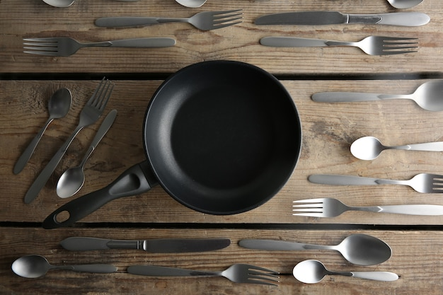Pan and silver cutlery on wooden table, top view