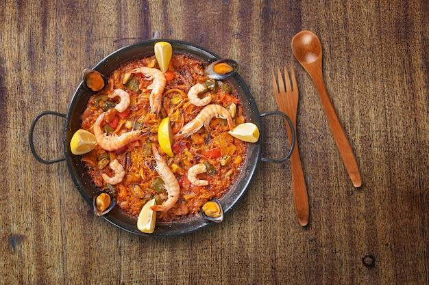 Pan of spanish paella on textured wooden table