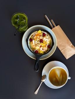 Сковорода с чизкейком или блинами и ягодами, чашкой кофе и маття на темном столе, вид сверху.