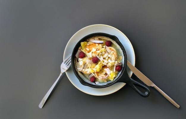 Сковорода с чизкейком или блинами и ягодами на темном столе, вид сверху.