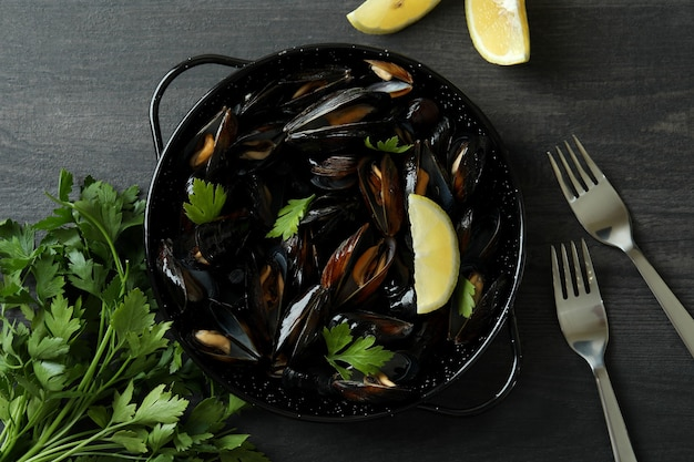 Pan with fresh mussels on dark wooden table