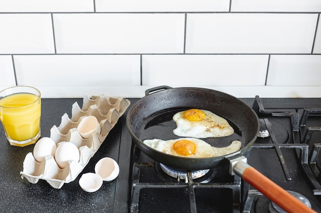 Pan with fried eggs and orange juice