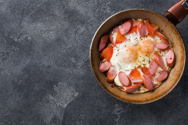 Pan with fried eggs sausages and tomatoes on the table.