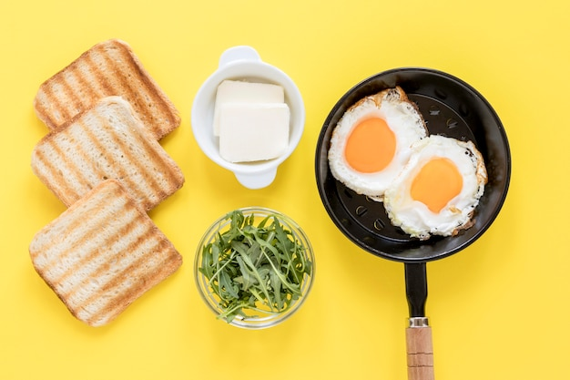 Pan with fried eggs and toast for breakfast