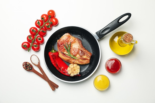 Сковорода с жареными стейками и ингредиентами для приготовления на белом фоне, вид сверху