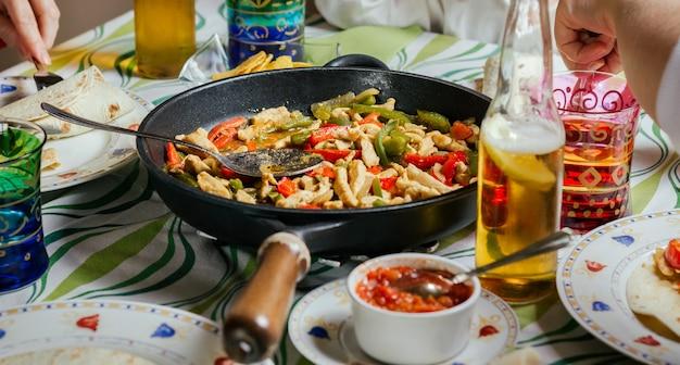 周りを食べている人々のグループと一緒にテーブルの上でメキシコ料理と一緒にパン