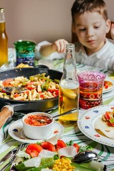 バックグラウンドで小さな男の子とテーブルの上にメキシコ料理とパン