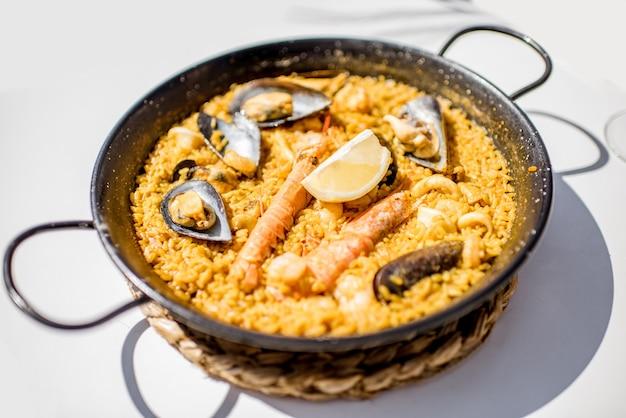 屋外の白いテーブルの上で、海のパエリア、バレンシアの米料理と一緒にパン