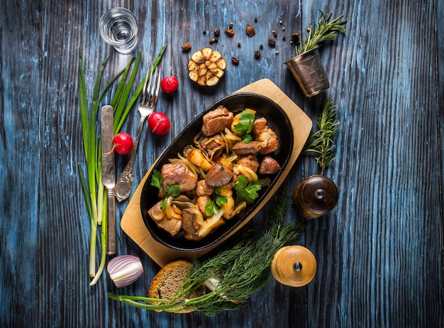 Pan with sliced roasted pork and vegetables on rustic wooden background