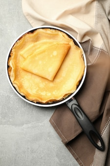 Pan with thin pancakes and kitchen towel on gray background