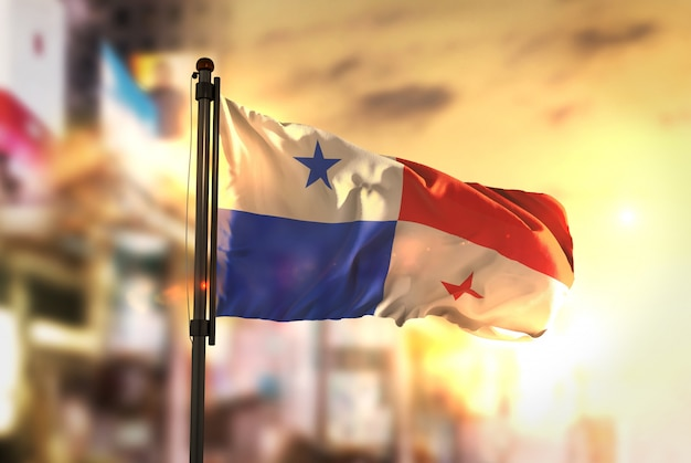 Panama flag against city blurred background at sunrise backlight