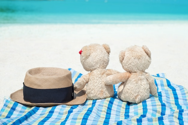 Panama hat and two teddy bears sitting sea view. love and relationship concept.