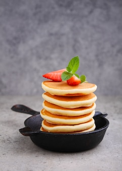 Pancake in a black pan with strawberries decorated with mint on a concrete table