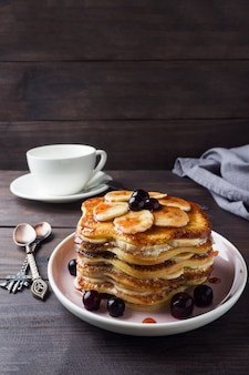 Pancake cake with bananas and berry syrup, selective focus, dark background.