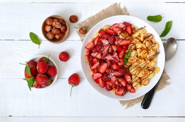 新鮮なイチゴと白い木製の表面上のナッツをボウルにパンケーキシリアル