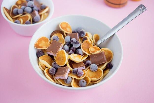 ピンクのテーブルにブルーベリーとチョコレートが入ったプレートのパンケーキシリアル小さなパンケーキが付いたトレンディでモダンな朝食