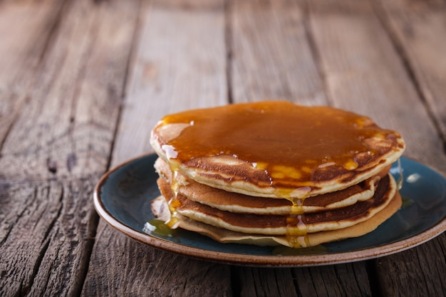 Pancake folded stack of with liquid honey on wooden background.