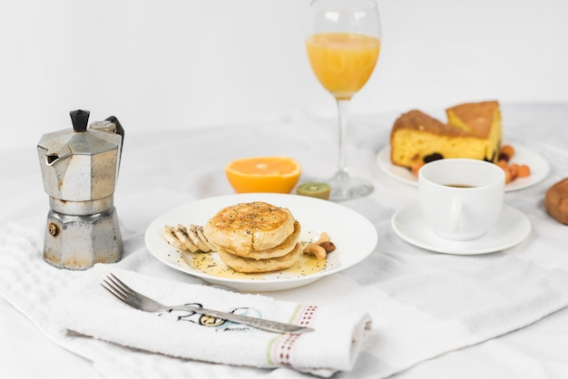 Pancake; fruit; juice; cake slice and coffee cup on breakfast table