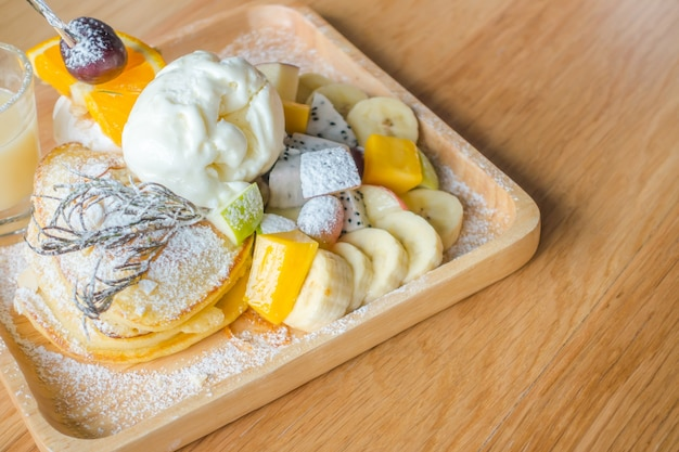 Pancake and fruit with ice cream on table .