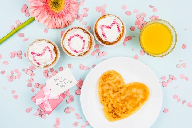 Блин на тарелке возле цветка, бокал, подарок с биркой и пирожные со словами мамы