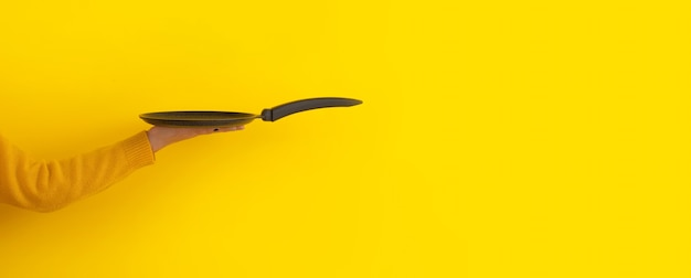 Pancake pan utensil on hand over yellow background, panoramic mock-up with space for text