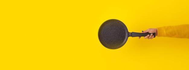 Pancake pan utensil in hand over yellow background, panoramic mock-up