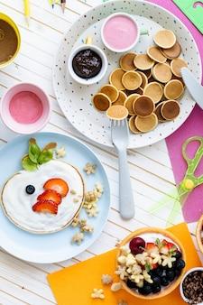 Pancake party, cibo per bambini con frutti di bosco freschi e yogurt