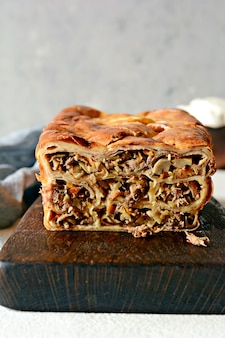 灰色の背景にキノコと肉のパンケーキパイ。パンの形のパンケーキケーキ。