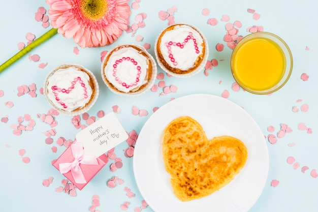 Pancake on plate near flower, glass, present with tag and cakes with mom words