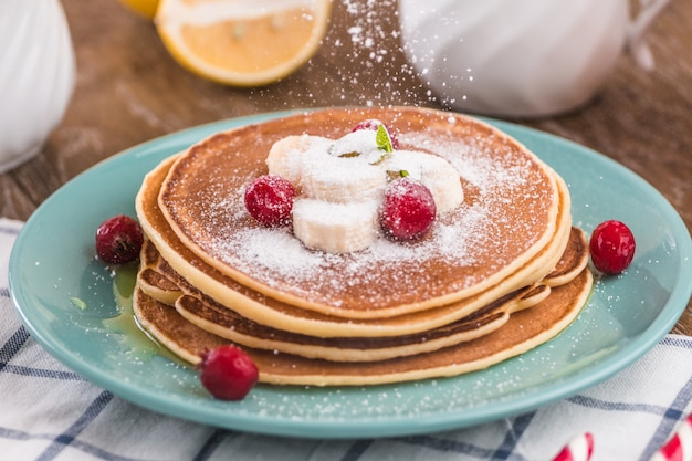 Pancake stack covered with honey, powdered sugar, banana and cranberries.
