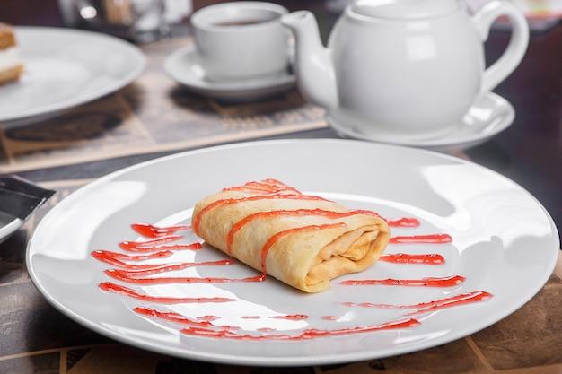 Pancake stuffed on a plate with jam