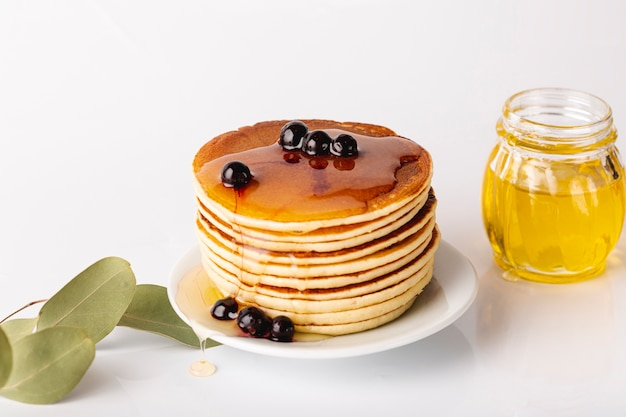Pancake tower on plate with blueberries and honey jar