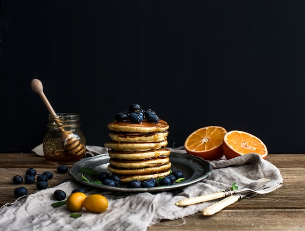 Pancake tower with fresh blueberries, oranges and mint on a rustic metal plate.