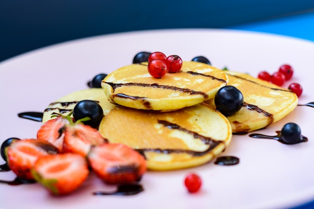 Pancake with berries and chocolate-doping on the pink plate