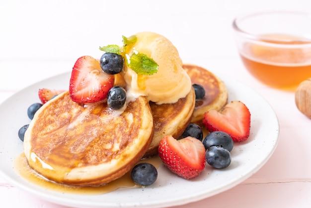 ブルーベリー、イチゴ、蜂蜜、バニラのアイスクリームのパンケーキ