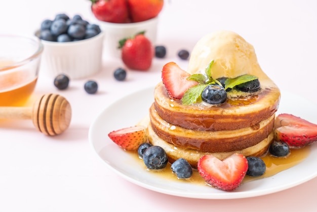 ブルーベリー、イチゴ、蜂蜜、バニラアイスクリームのパンケーキ