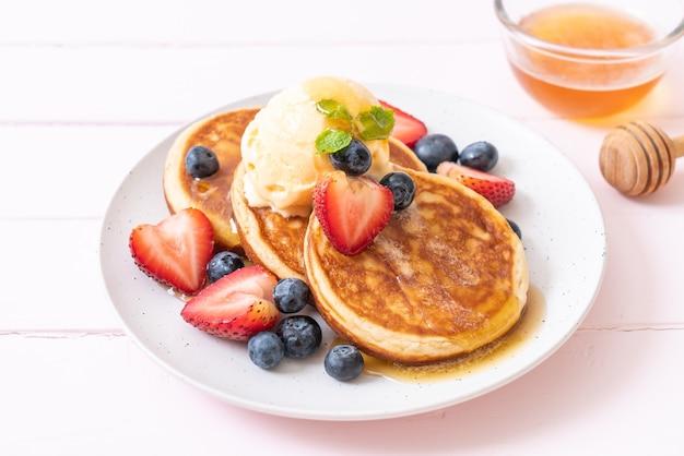 Pancake with blueberries, strawberries, honey and vanilla ice-cream